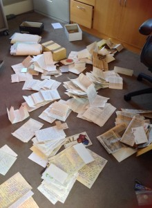 Piles of photos and letters to be scanned
